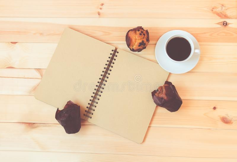 Pusty notatnik, kawa i słodka bułeczka na drewnianym tle, zdjęcia stock