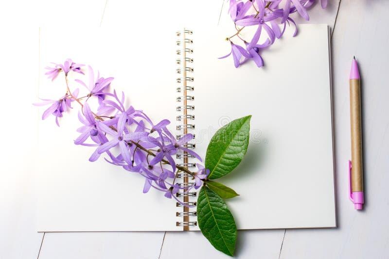 Pusty notatnik z piórem i purpurami kwitnie na białym drewnianym backg obraz royalty free
