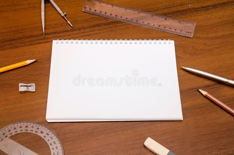 Pusty notepad, pióro, ołówkowy władca kompas na ciemnym drewnianym tle obraz royalty free