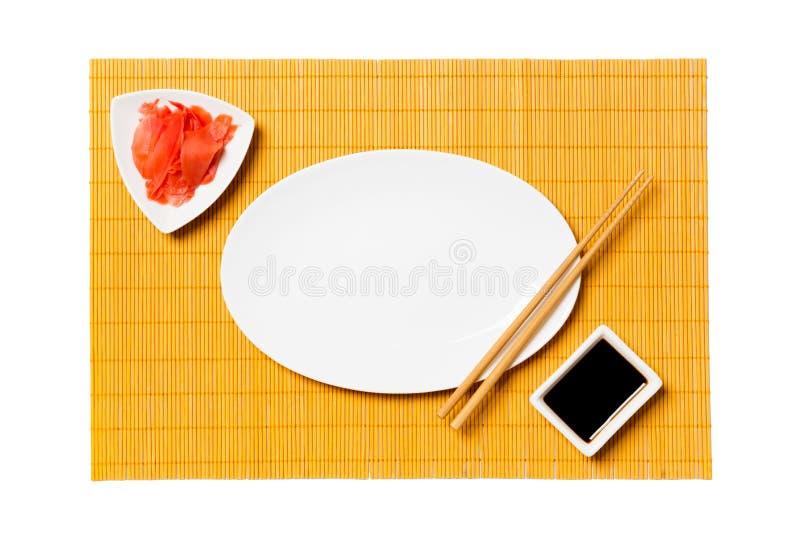 Pusty owalny bielu talerz z chopsticks dla suszi i soj kumberlandu, imbir na żółtym bambus maty tle Odg?rny widok z kopii przestr zdjęcie stock