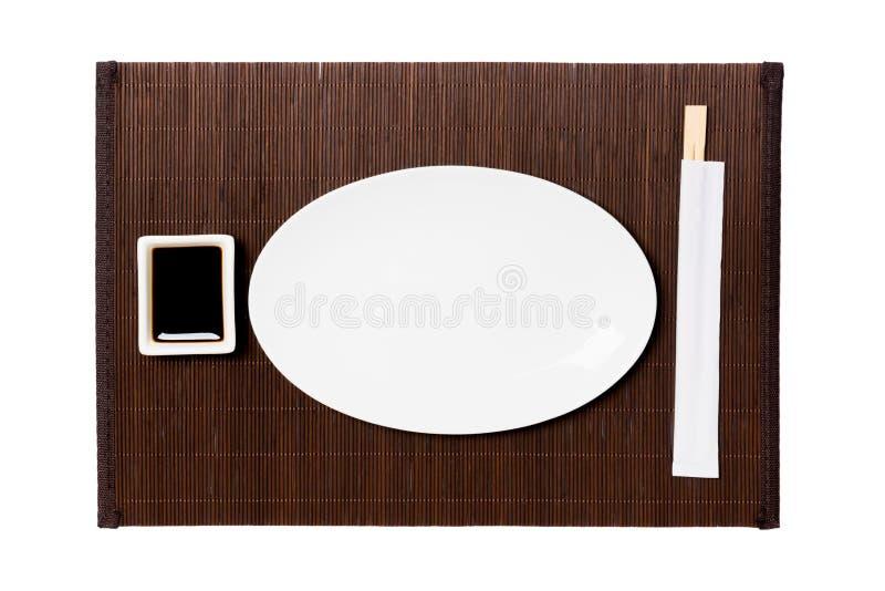 Pusty owalny bielu talerz z chopsticks dla suszi i soj kumberlandu na ciemnym bambusie matuje tło Odgórny widok z kopii przestrze zdjęcie royalty free