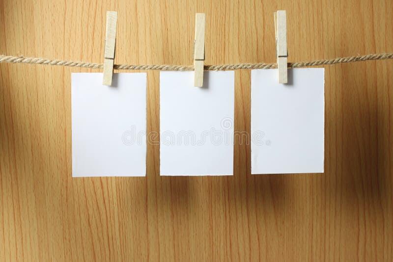 Pusty papier wiesza na brąz arkanie z Drewnianymi papierowymi klamerkami na w zdjęcie stock