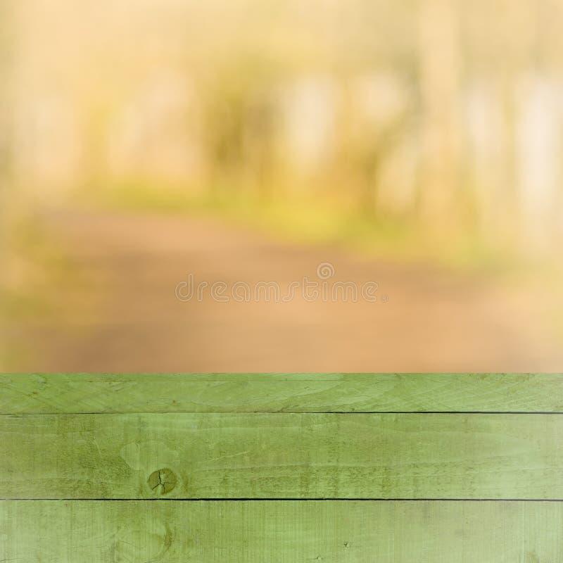 Pusty perspektywy zieleni drewno nad zamazanymi drzewami z bokeh tłem dla produktu pokazu montażu, zdjęcia stock