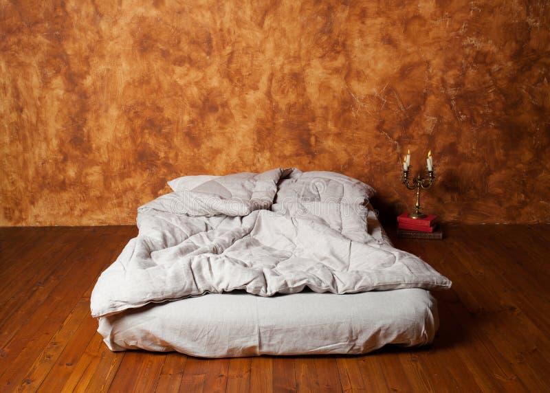 Pusty pokój w loft z materac jako łóżkowy, brąz ściana, wo zdjęcie stock