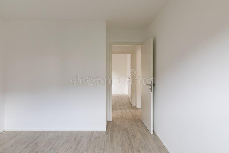 Pusty pokój z biel ścianami i otwarte drzwi na dobrze fotografia stock