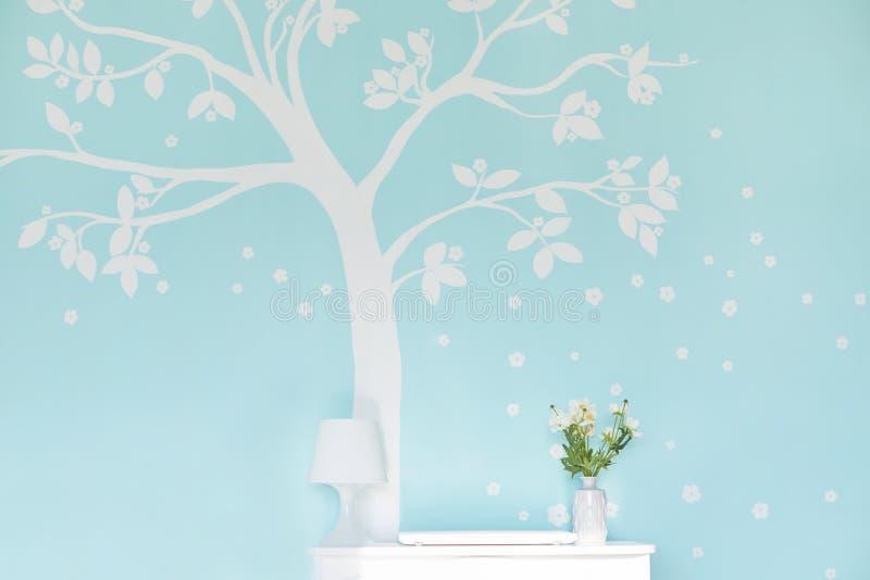 Pusty pokój z bielu stołem, lampa, waza z kwiatami przeciw bławej ścianie z drukowanym drzewem Wygodny mieszkanie lub miejsce pra obrazy royalty free