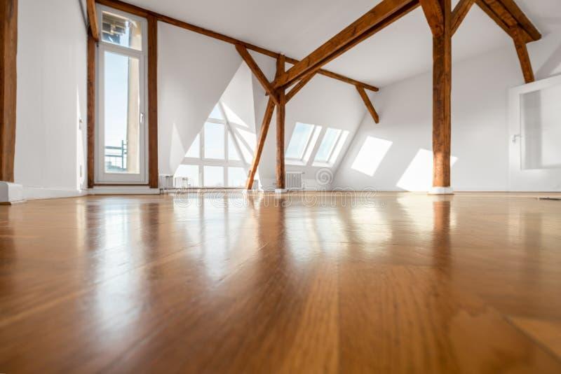 Pusty pokój z drewnianą podłoga i dachowymi promieniami - apartament na najwyższym piętrze fotografia stock