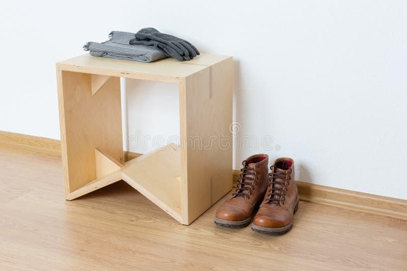 Pusty pokój z drewnianym stołem i skórzanymi butami fotografia royalty free