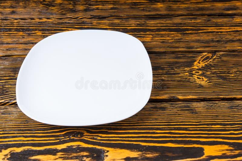 Pusty prosty bielu talerz na drewnianym tle zdjęcie stock