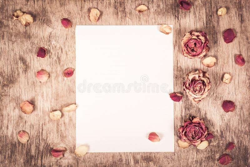 Pusty prześcieradło papier i wysuszone róże Puste miejsce notatka na drewnianym tle Wysuszone róże i płatki kosmos kopii fotografia stock