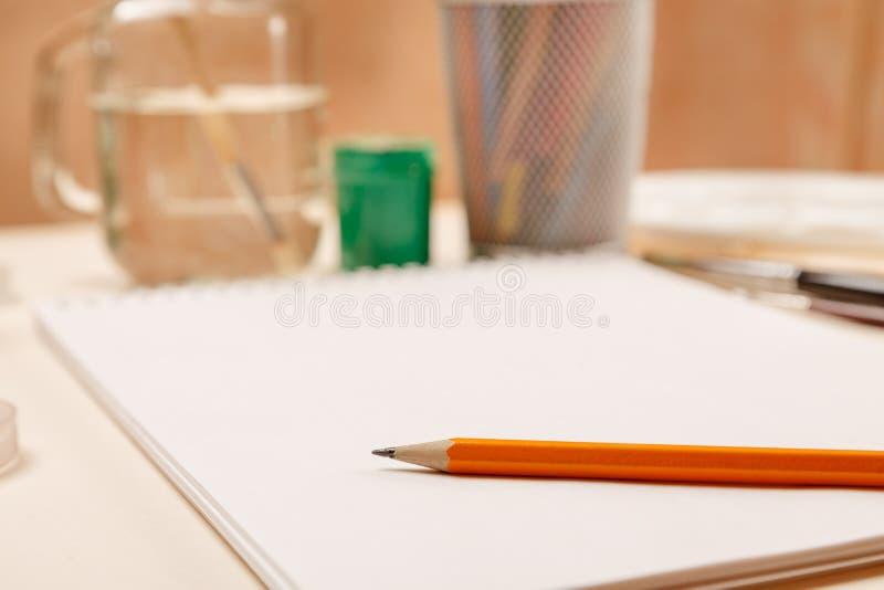 Pusty prześcieradło papier z ołówkiem na nim i inny materiał dla rysować, selekcyjna ostrość obraz stock