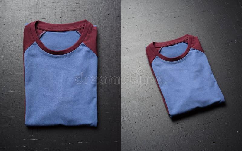 Pusty rocznik składająca koszulka kłama na czarnym drewnianym stołowym tle Frontowy widok Amerykańskich modnisiów retro klasyk fotografia stock