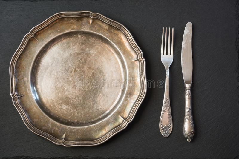 Pusty rocznika metalu talerz z silverware na czerni, z kopii przestrzenią dla twój przepisu lub menu Menu karta dla restauracj obraz royalty free