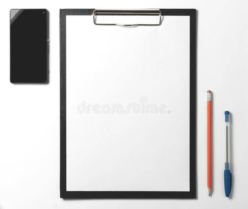 Pusty schowek, smartphone, pióro i ołówek na białym tle, zdjęcia royalty free