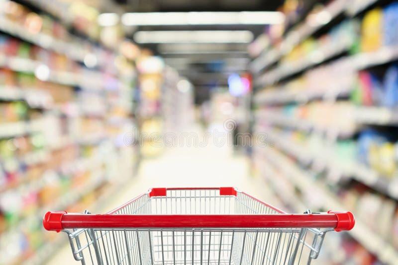 Pusty wózek na zakupy z abstrakcjonistycznej plama supermarketa dyskontowego sklepu nawy defocused tłem obrazy stock