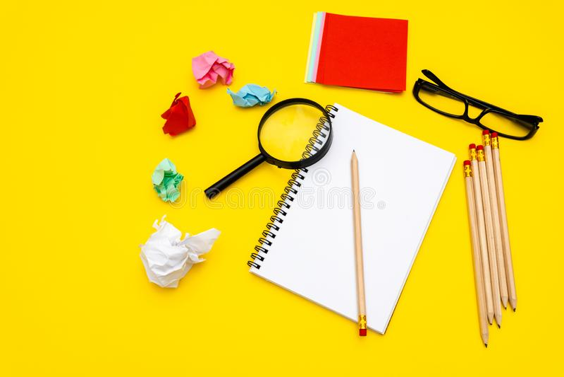Pusty writing ochraniacz dla pomys??w i inspiraci na barwionym tle Powiększać - szkło na górze notepad Wokoło notepads kłamstw obraz stock