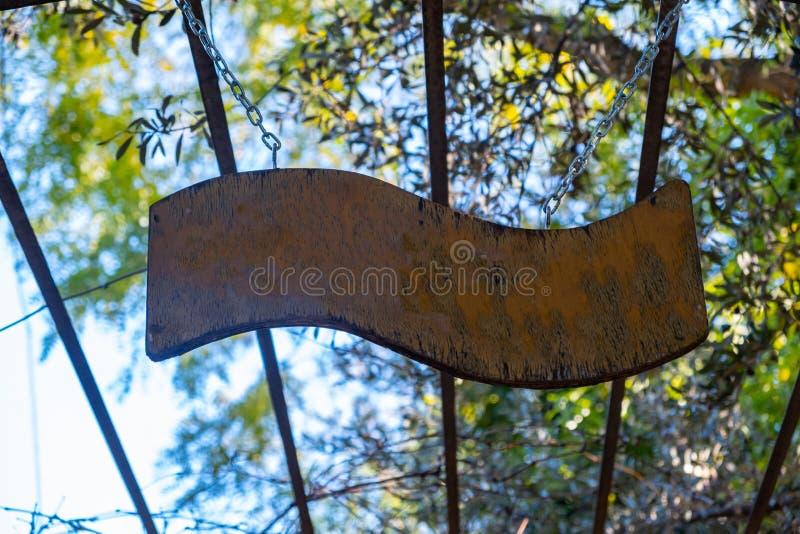 Pusty znak drewniany wiszący na konstrukcji metalowej, niebieskie niebo i tło drzew fotografia stock