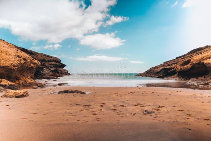 Pustynna plaża z skałami i jasnym niebieskim niebem obraz royalty free