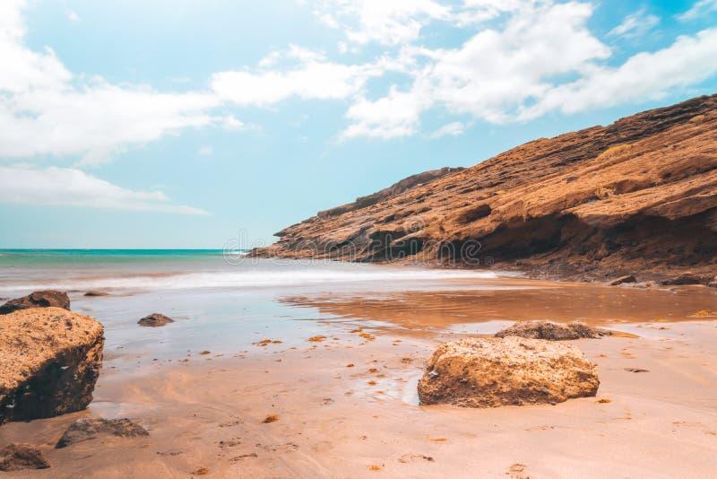 Pustynna plaża z skałami i jasnym niebieskim niebem zdjęcie royalty free