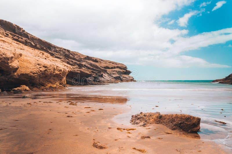 Pustynna plaża z skałami i jasnym niebieskim niebem fotografia stock