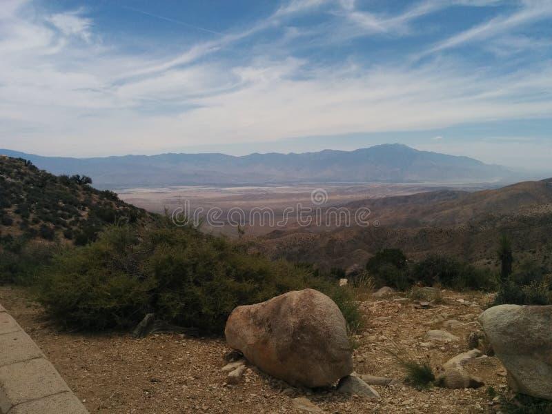 Pustynny góra krajobraz z wispy głazem w przedpolu i chmurami fotografia royalty free