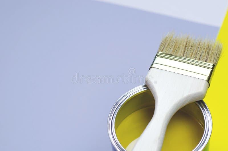 A puszka żółta farba z muśnięciem na kolorze żółtym z białym tłem obraz royalty free