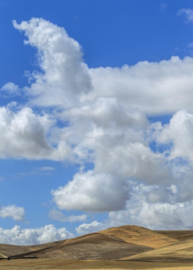 Puszyste chmury nad kołysań się wzgórza fotografia stock
