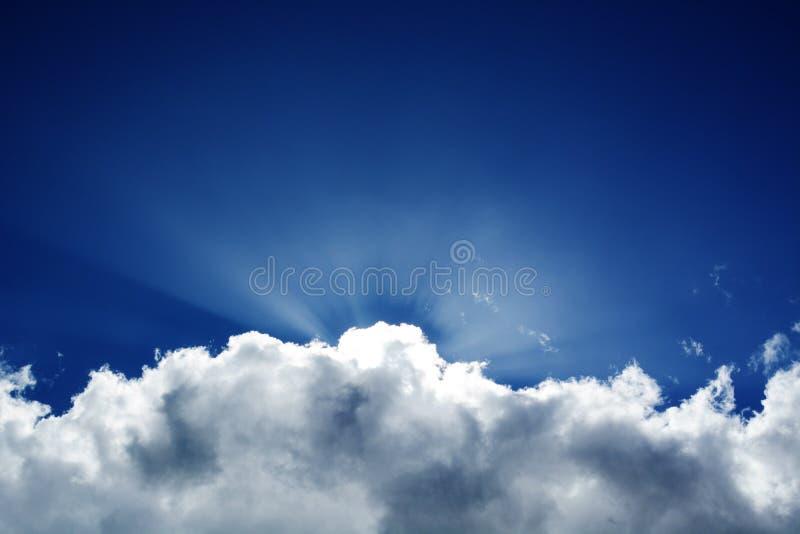 Puszystego chmury niebieskiego nieba zmierzchowi promienie fotografia stock