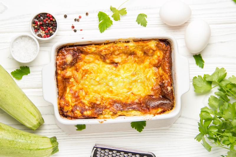 Puszysty omlet piec z zucchini, dzieciaka zdrowy ?niadanie, smakowita potrawka Na bia?ym drewnianym tle w pieczenia naczyniu, fotografia stock