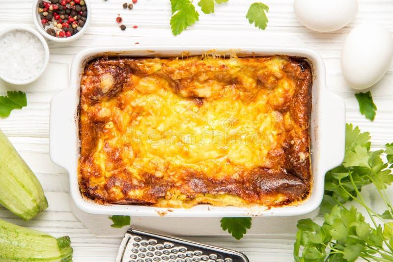 Puszysty omlet piec z zucchini, dzieciaka zdrowy ?niadanie, smakowita potrawka Na bia?ym drewnianym tle w pieczenia naczyniu, obrazy royalty free