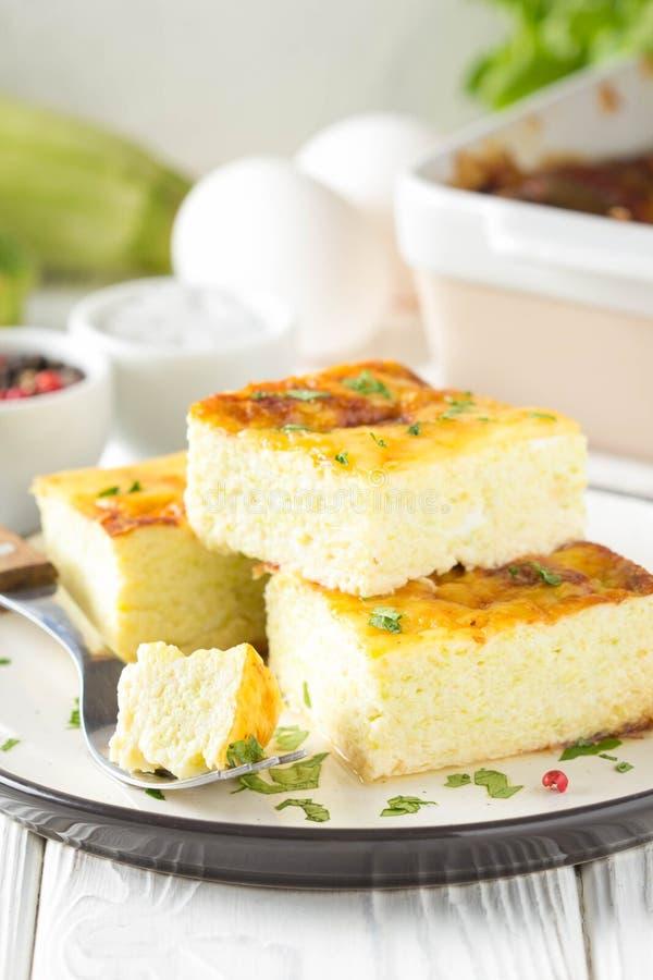 Puszysty omlet piec z zucchini, dzieciaka zdrowy ?niadanie, wy?mienicie potrawka Na bia?ym drewnianym tle obraz royalty free