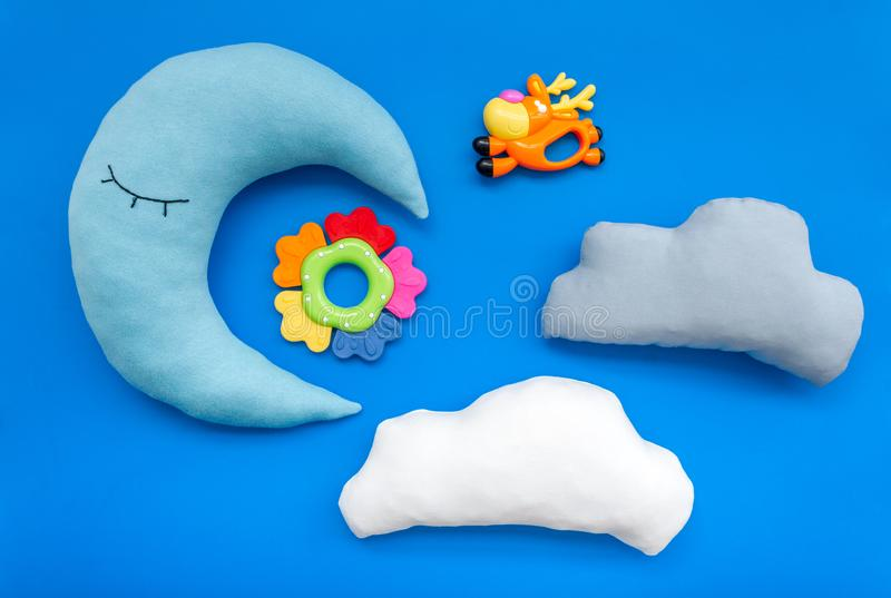 Put baby into bed with moon pillow, clouds and toy on blue background top view royalty free stock photos