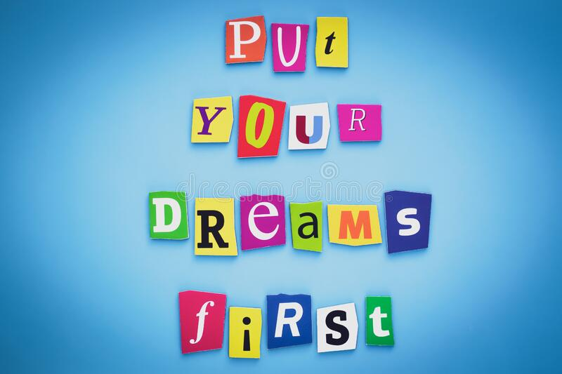 Put your dreams first. Positive thinking concept. Text of cut colorful letters on blue background. Writing on banner, card. royalty free stock photo