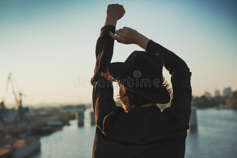 Put your hands in the air. Dreaming mood street style photo wiht back young girl with hat royalty free stock images