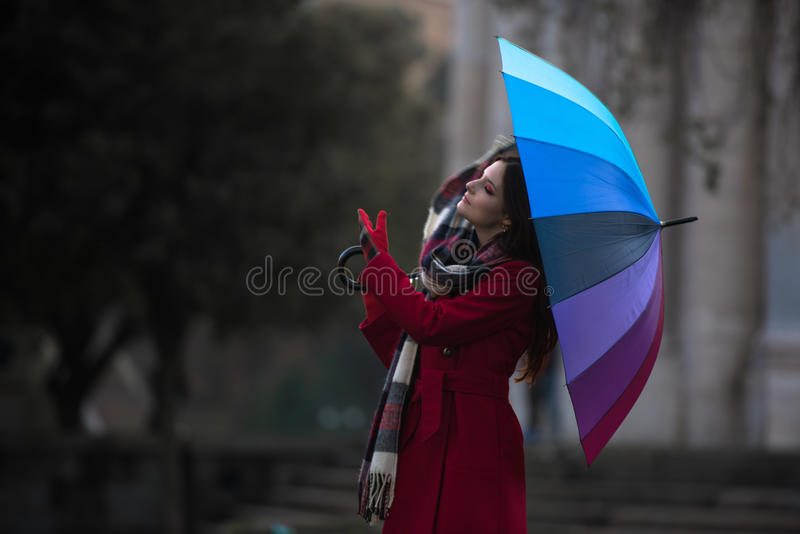Put on your scarf. Beautiful portrait of a stunning and gorgeous redhead french girl with small freckles and long hair trying to put on her long scarf to protect stock photo