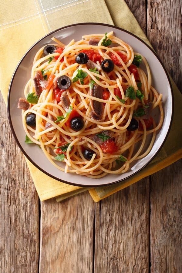 Putanesca di alla degli spaghetti con le acciughe, i pomodori, l'aglio ed il bl fotografia stock libera da diritti
