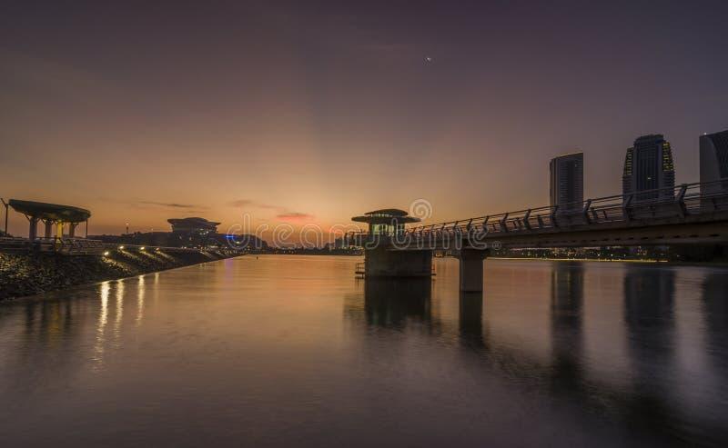 Putrajaya, Malasia 21 de febrero de 2015: Opiniones de los edificios del gobierno del parque húmedo en Putrajaya durante puesta d foto de archivo libre de regalías