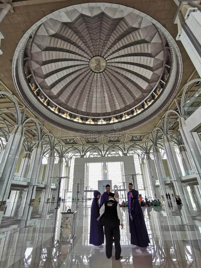 PUTRAJAYA, MALAYSIA-SEPTEMBER 14, 2019:  A group of non-Muslim foreign tourist take a tour inside Sultan Mizan mosque with trained. Guide explaining about Islam royalty free stock image