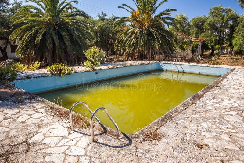 Putrid zieleni woda w zaniechanym pływackim basenie zdjęcia royalty free