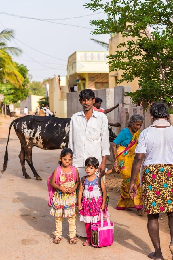PUTTAPARTHI, ANDHRA PRADESH, ÍNDIA - 9 DE JULHO DE 2017: Família indiana em uma rua da vila vertical foto de stock royalty free