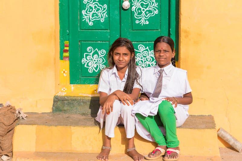 PUTTAPARTHI, ANDHRA PRADESH, ÍNDIA - 9 DE JULHO DE 2017: Menina dois indiana bonito que senta-se na entrada Copie o espaço para o foto de stock