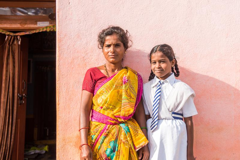 PUTTAPARTHI, ANDHRA PRADESH, INDIA - JULY 9, 2017: Indian woman in sari and girl in school uniform. Copy space for text. Close-up. PUTTAPARTHI, ANDHRA PRADESH stock photo
