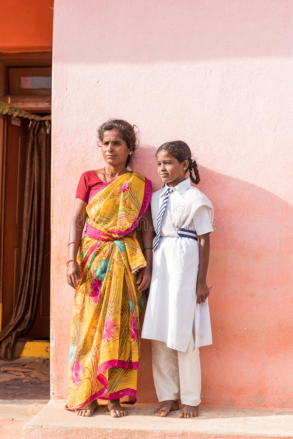 PUTTAPARTHI, ANDHRA PRADESH, INDIA - JULY 9, 2017: Indian woman in sari and girl in school uniform. Copy space for text. Vertical. PUTTAPARTHI, ANDHRA PRADESH royalty free stock photography