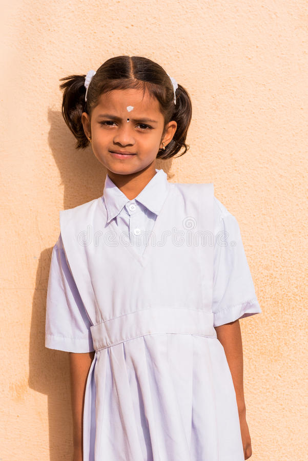 PUTTAPARTHI, ANDHRA PRADESH, INDIA - JULY 9, 2017: Portrait of a cute indian girl in white dress. Close-up. Vertical. stock photo