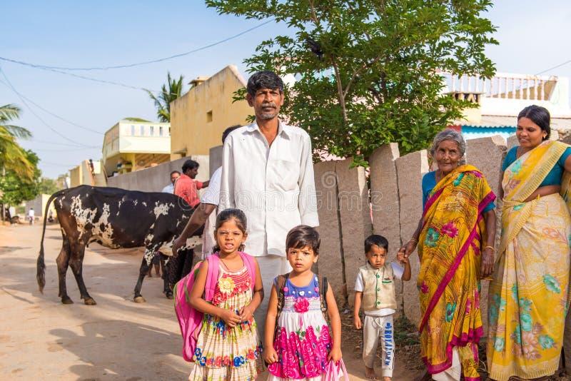 PUTTAPARTHI, ANDRA PRADESH, INDIA - JULI 9, 2017: Indische familie in een dorpsstraat Exemplaarruimte voor tekst royalty-vrije stock fotografie