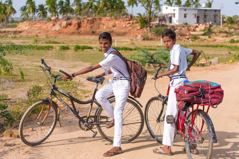 PUTTAPARTHI, ANDRA PRADESH, INDIA - JULI 9, 2017: Twee Indische jongens op fietsen Exemplaarruimte voor tekst stock foto's