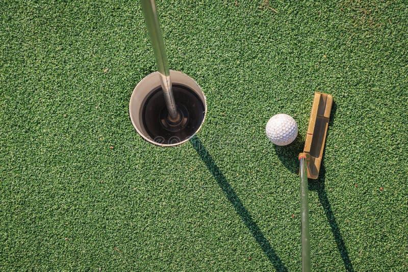 Putter med golfboll och hålet royaltyfri fotografi