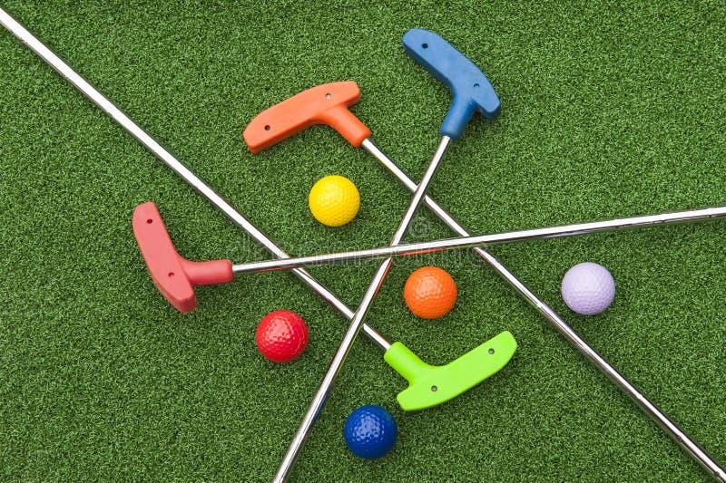 Putters assortis et boules de golf miniature image libre de droits