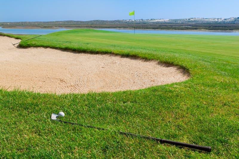 Putters en bal die op golfcursus liggen stock afbeelding