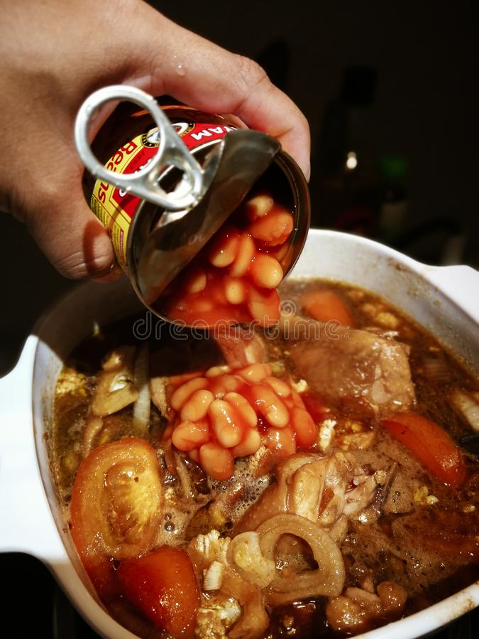 Putting the baked beans from the tin can container into the cChicken with soy sauce, or known stock photography